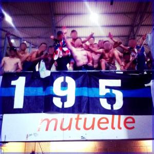Le 30 aout 2013, les Turons 1951 se faisaient remarquer au stade de Nancy. On peut les voir effectuer des « quenelles inversées ». Nicolas est présent sur la photo, il tente manifestement de dire bonjour à quelqu'un. Indice : bermuda, bourrelets, montre…